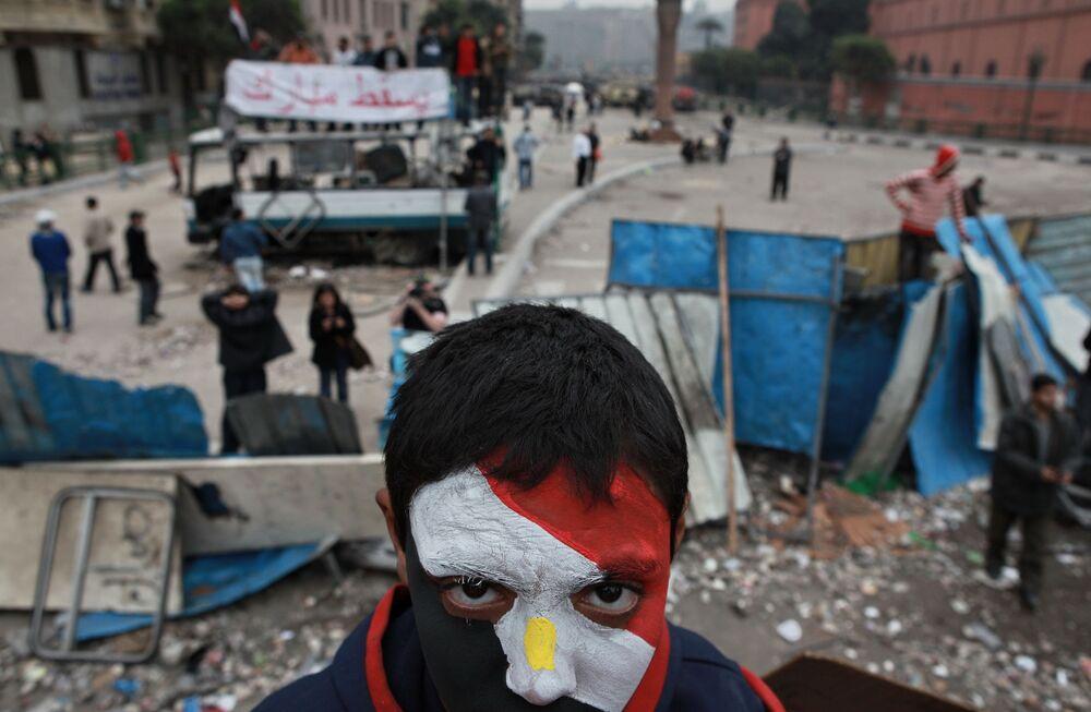 Apoiador da oposição de rosto pintado com cores da bandeira egípcia na praça Tahrir, Cairo