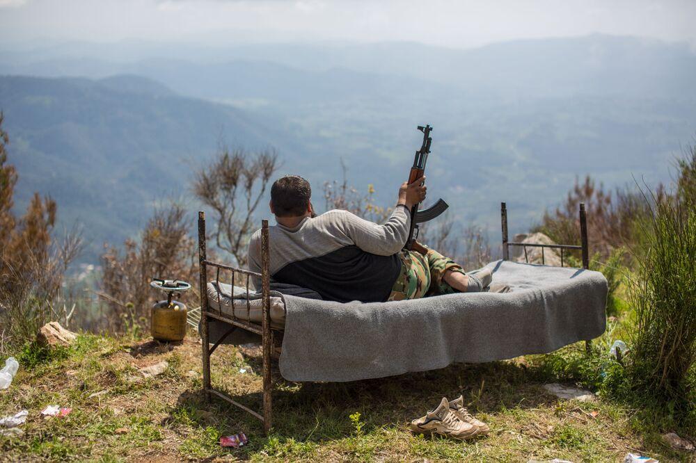 Soldado sírio deitado ao ar livre na cidade de Kesab