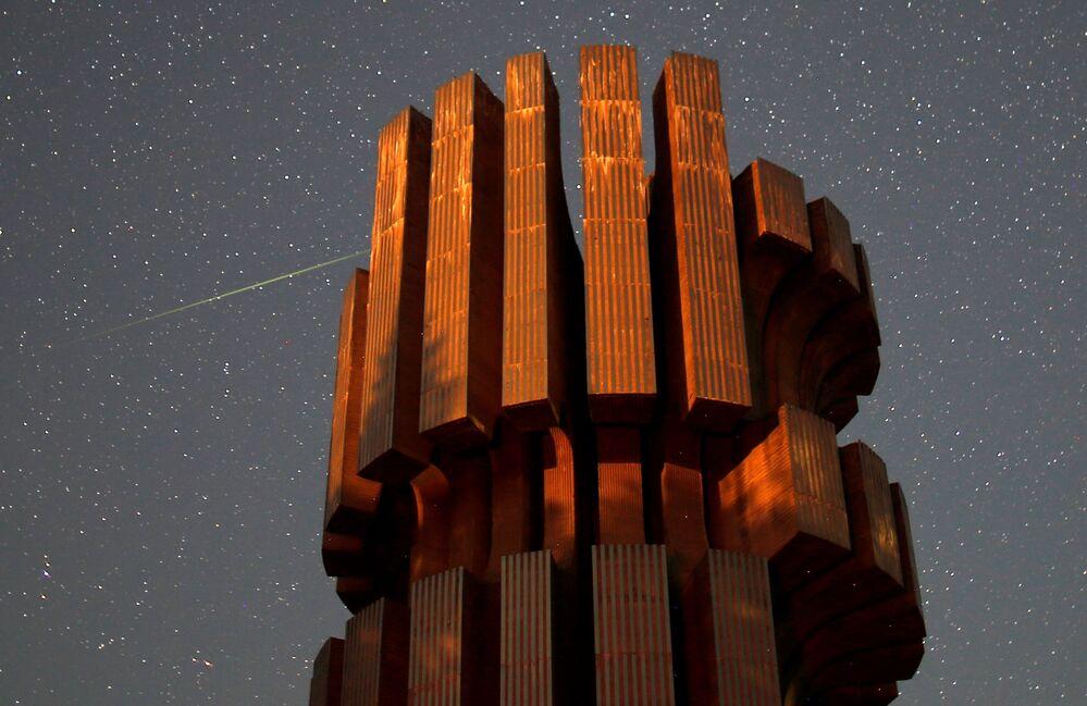 Chuva de meteoros Perseidas sobre o monumento da revolução nas montanhas de Kozara, em Bósnia e Herzegovina
