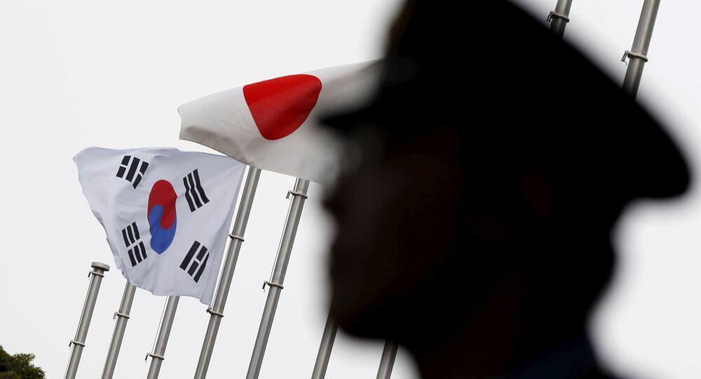 Policial com bandeiras da Coreia do Sul e do Japão em fundo
