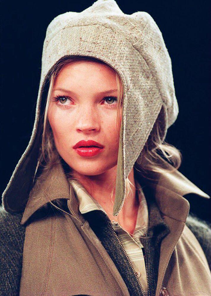 Supermodelo britânica Kate Moss com um chapéu e casaquinho de camurça desfilando para Anne Klein