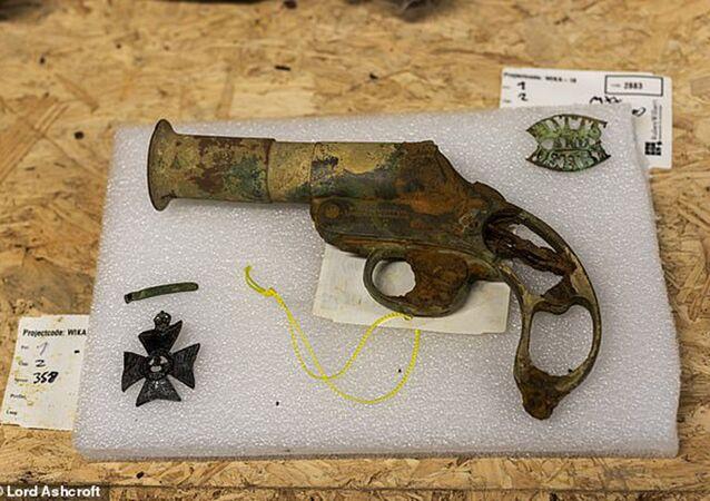 Revólver e medalha da 1ª Guerra Mundial em campo belga