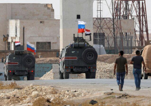 Bandeiras da Rússia e da Síria hasteadas em veículos militares na cidade russa de Manbij, em 15 de outubro de 2019.