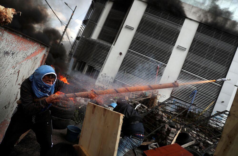 Manifestante atira de uma arma artesanal durante protesto em Quito, no Equador