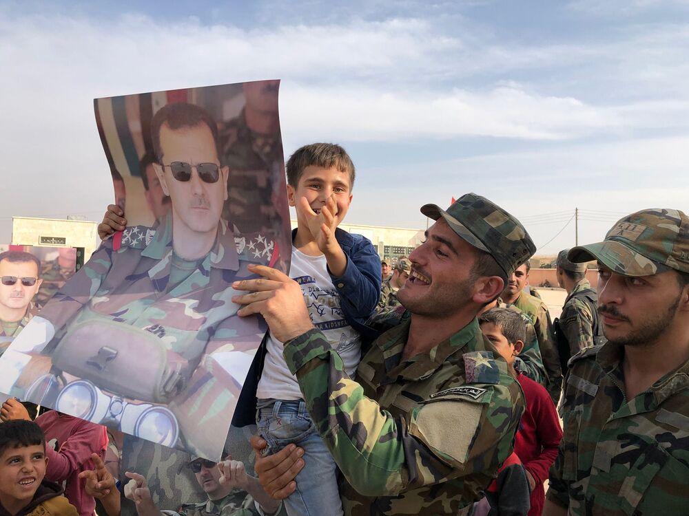 Crianças e militares com retratos do presidente da Síria, Bashar al-Assad, na cidade Manbij libertada pelo Exército governamental sírio