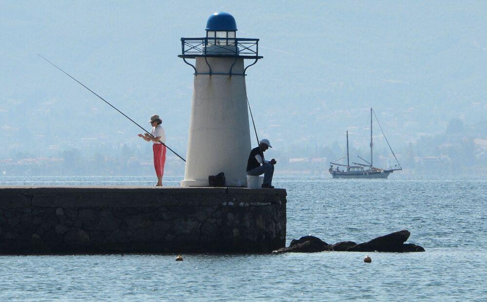 Visitantes pescam perto de farol no Golfo Sul de Eubea no mar Egeu