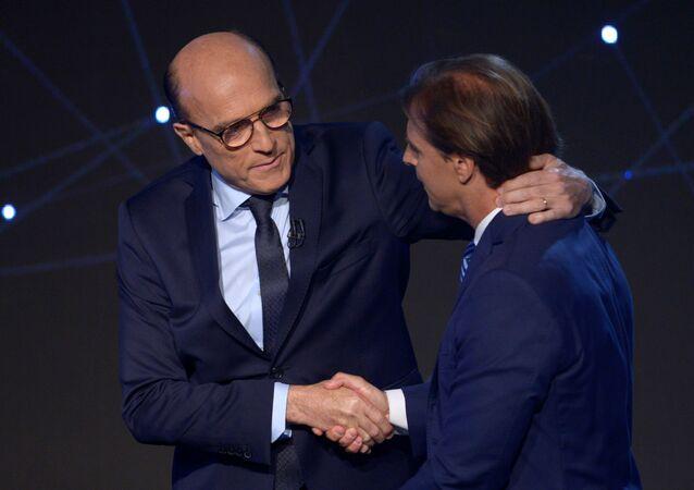 Os dois principais candidatos à presidência do Uruguai, Daniel Martínez, da Frente Ampla (à esquerda) e Luis Lacalle Pou, do Partido Nacional, (à direita) se cumprimentam durante um debate presidencial no Canal 4, em Montevidéu no dia 1º de outubro.