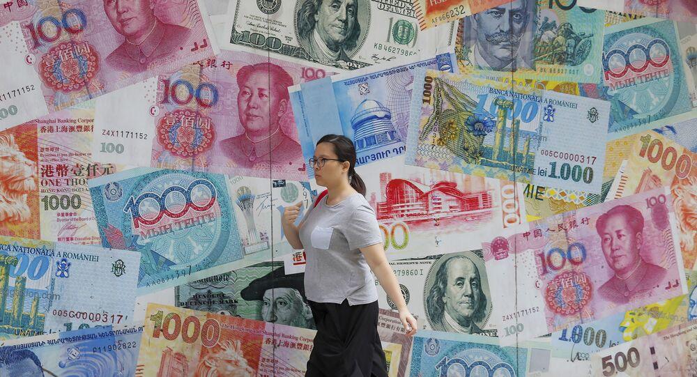Mulher passa em frente de imagens de dólares e da moeda chinesa