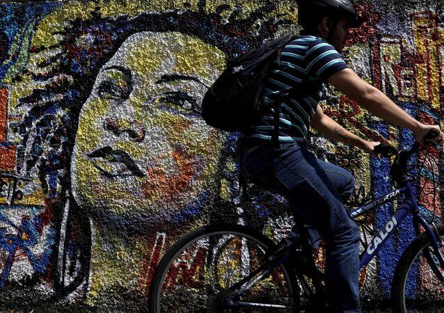 Homem passa em frente ao grafite com o rosto de Marielle Franco, vereadora do PSOL assassinada no em março de 2018.