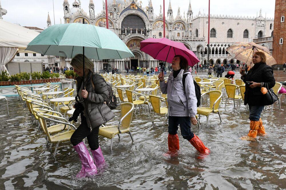 Turistas com botas de plástico andando pela Praça de San Marco inundada