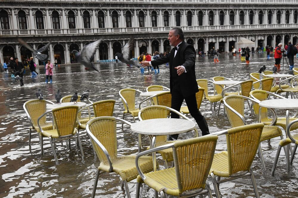 Homem espanta pombos na Praça de San Marco durante a inundação