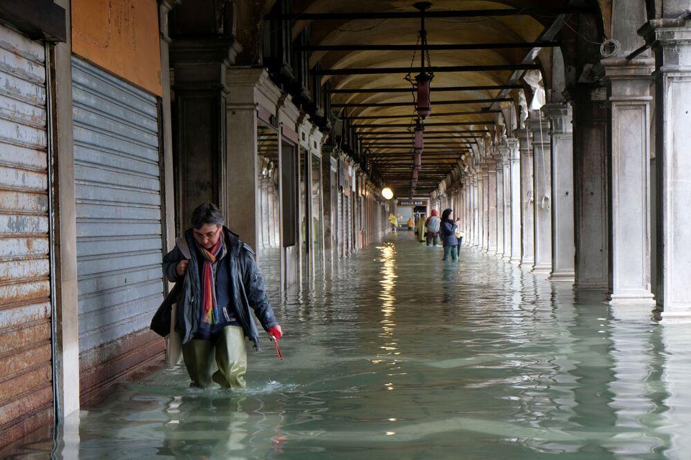 Mulher caminha com cuidado com água até o joelho na Praça de San Marco