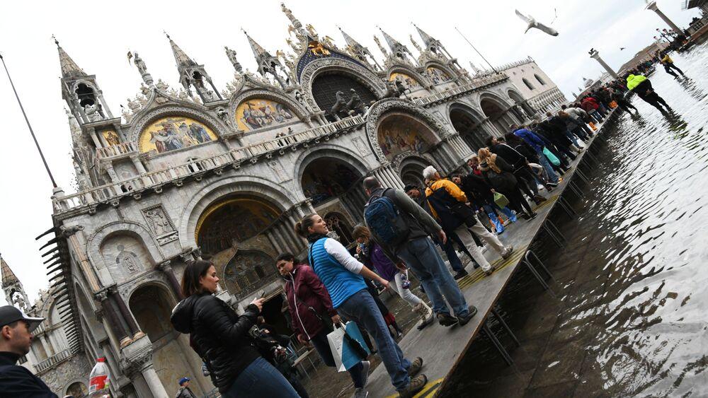 Turistas andam sobre passadiço improvisado durante inundação na Praça de San Marco, Veneza