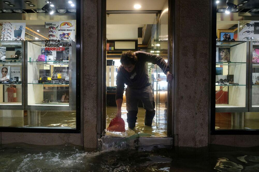 Trabalhador de ótica em Veneza remove a água do interior da loja