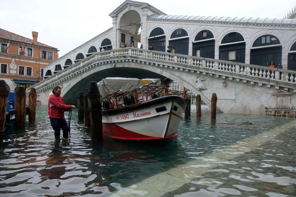 Homem amarra barco a poste de madeira durante inundação