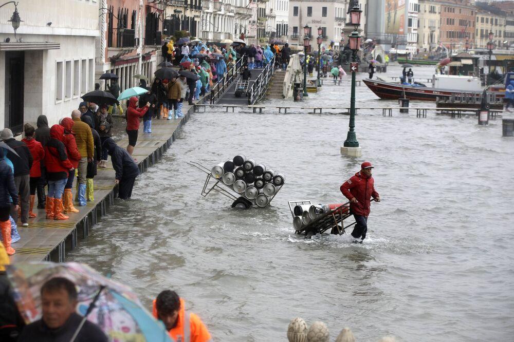 Homem carrega cilindros pela água enquanto turistas andam por passadiço improvisado