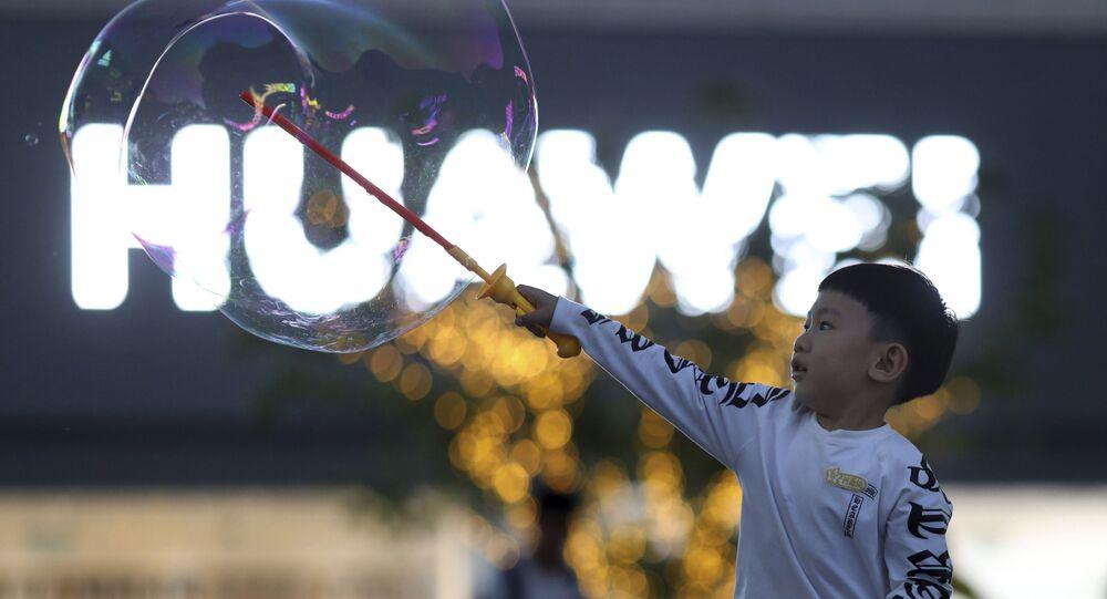 Criança brinca próxima ao logo da empresa Huawei, em Pequim (foto de arquivo)
