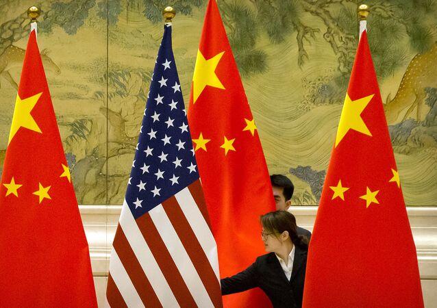 Funcionários organizam bandeiras dos Estados Unidos e China antes de sessão de negociações
