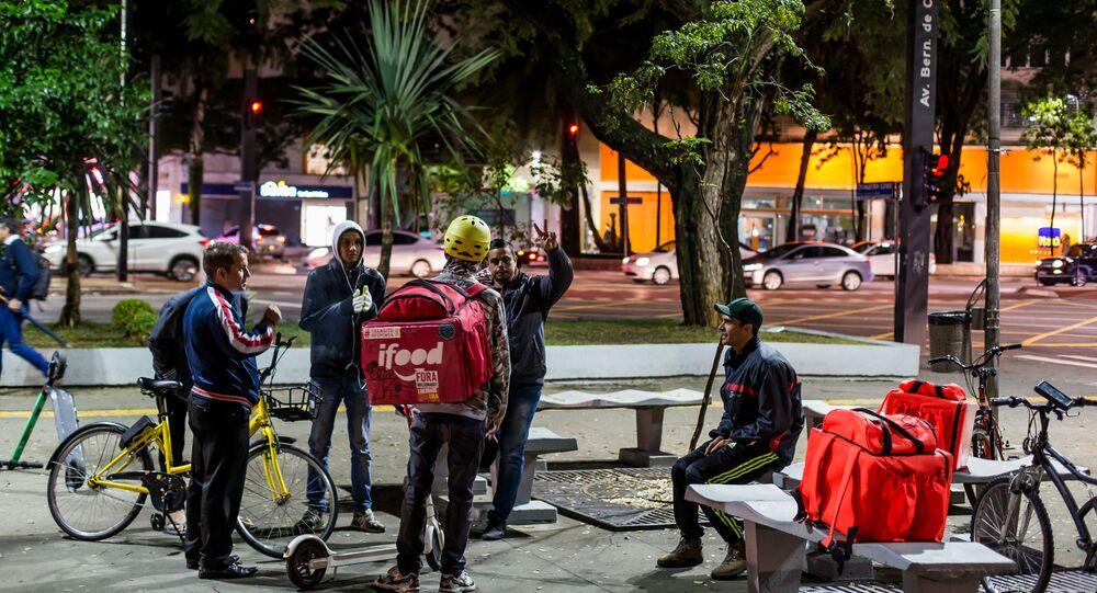 Entregadores de fast-foods por aplicativo que utilizam bicicletas e patinetes para se locomover, se reúnem na praça Osvaldo Cruz, em São Paulo, à espera de chamadas