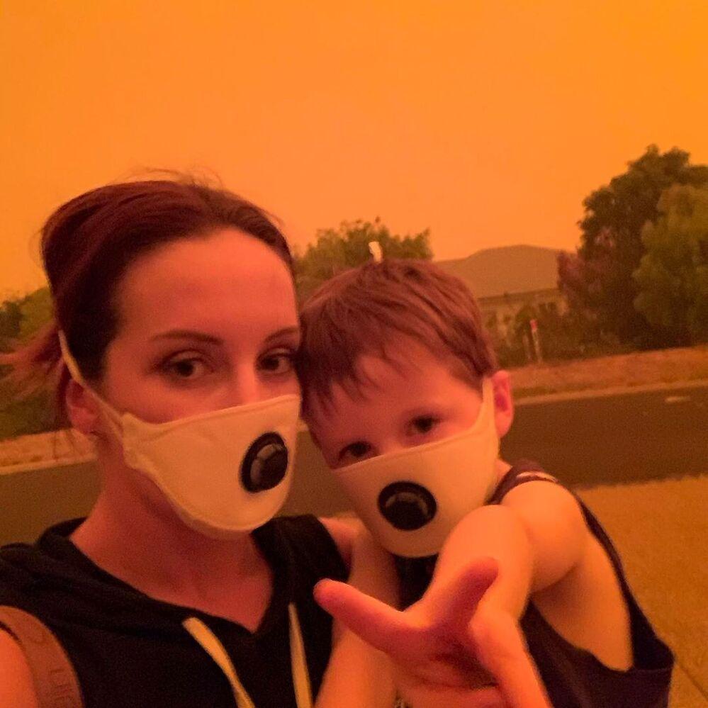 Mãe e filho usam máscaras para se proteger da fumaça causada pelos incêndios na Austrália