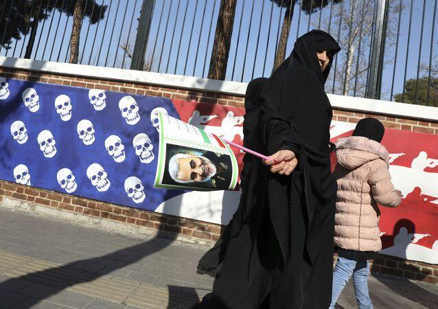 Mulher iraniana caminha com retrato do general Qassem Soleimani perto de muro com representação de bandeira dos Estados Unidos