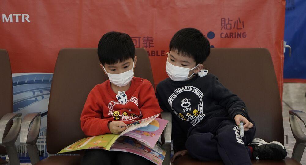 Crianças leem revista utilizando máscaras em estação de trem em Hong Kong.
