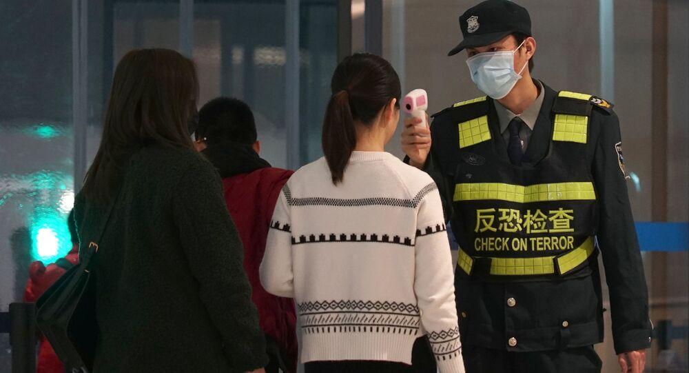 Passageiras passam por controle térmico no Aeroporto Internacional Tianhe, em Wuhan, China (foto de arquivo)