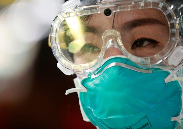 Funcionária de aeroporto usa máscara e óculos para se proteger de surto de coronavírus (foto de arquivo)