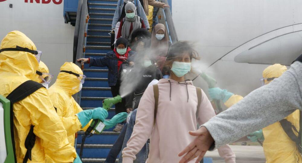 Médicos borrifam cidadãos indonésios com antisséptico após serem evacuados de cidade epicentro de surto de coronavírus na China, Wuhan