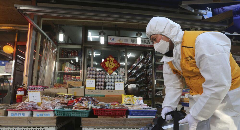 Para deter propagação do coronavírus, homem aplica desinfetante em mercado na China