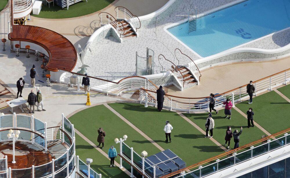 Passageiros tomam banho de sol em navio de cruzeiro colocado em quarentena, no porto de Yokohama, ao sul de Tóquio, no Japão
