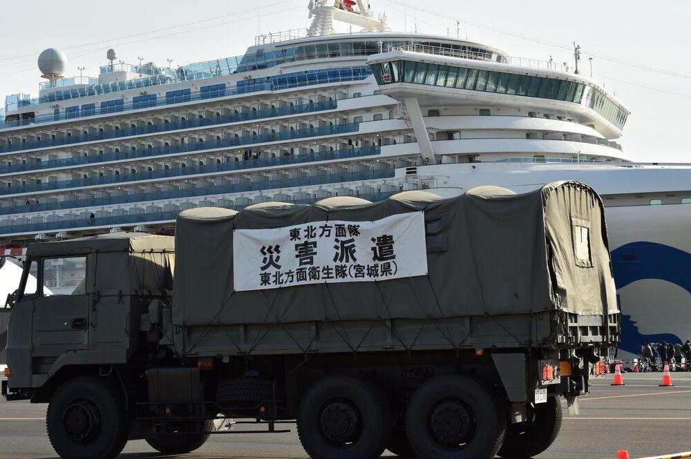 Corpo de Defesa de Saúde do Japão entra na área restrita, próxima ao navio de cruzeiro Diamond Princess, ancorado no porto de Yokohama, no Japão