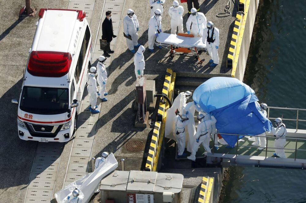 Paciente com coronavírus (coberto com lençol azul) é transferido do navio de cruzeiro Diamond Princess para uma base policial marítima japonesa