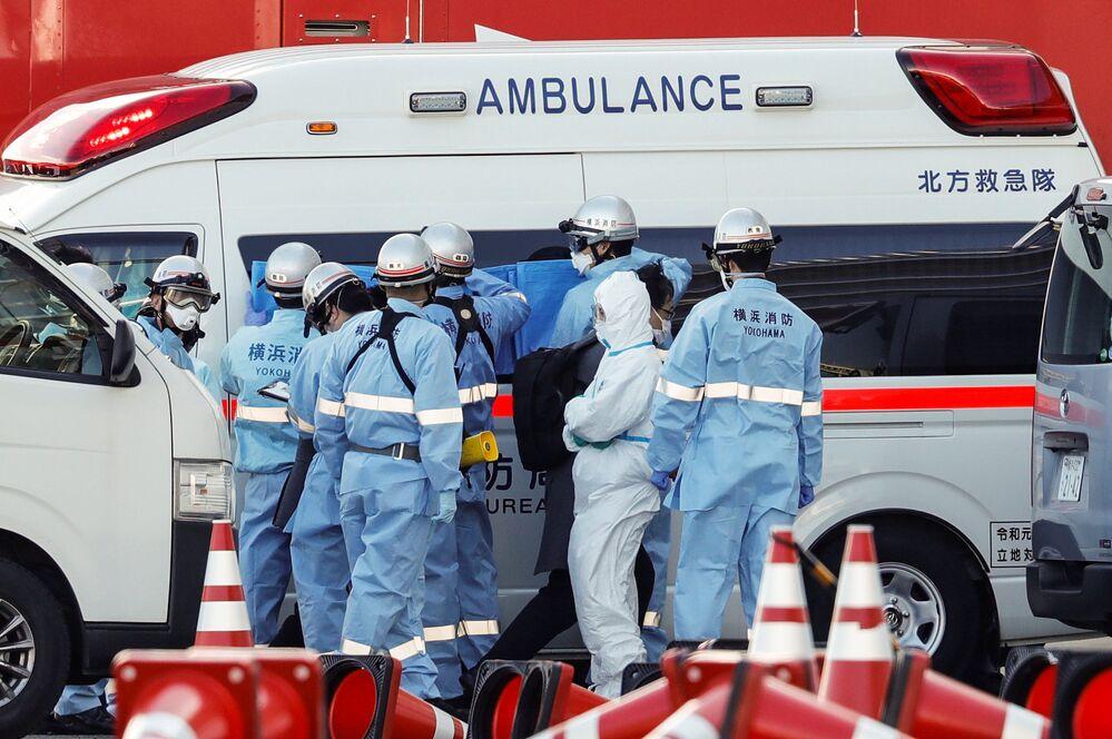 Bombeiros usam roupa de proteção e seguram telas para proteger a privacidade de pacientes infectados com o coronavírus, em 6 de fevereiro de 2020