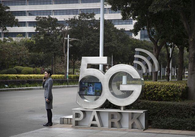 Funcionária da Huawei fala ao celular em escritório da empresa em Shenzhen, na China, em dezembro de 2019