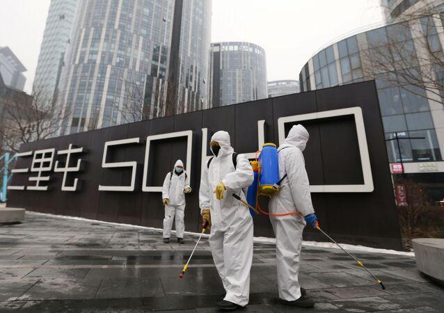 Trabalhadores protegidos desinfectam complexo comercial, após surto do novo coronavírus no país, Pequim, China, 13 de fevereiro de 2020