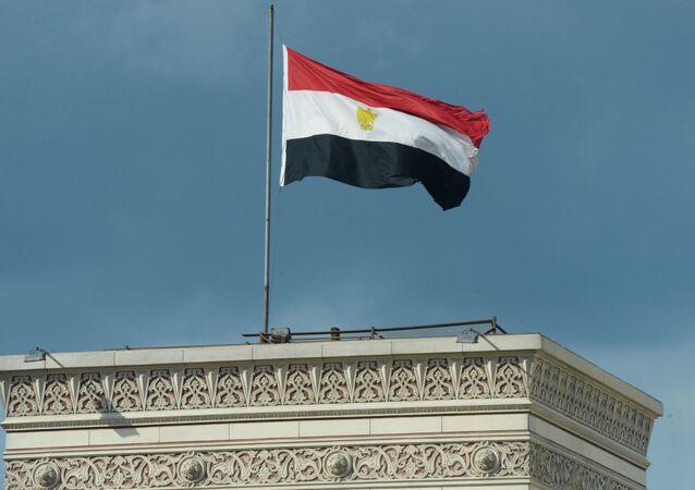Bandeira do Egito tremula sobre prédio no Cairo.