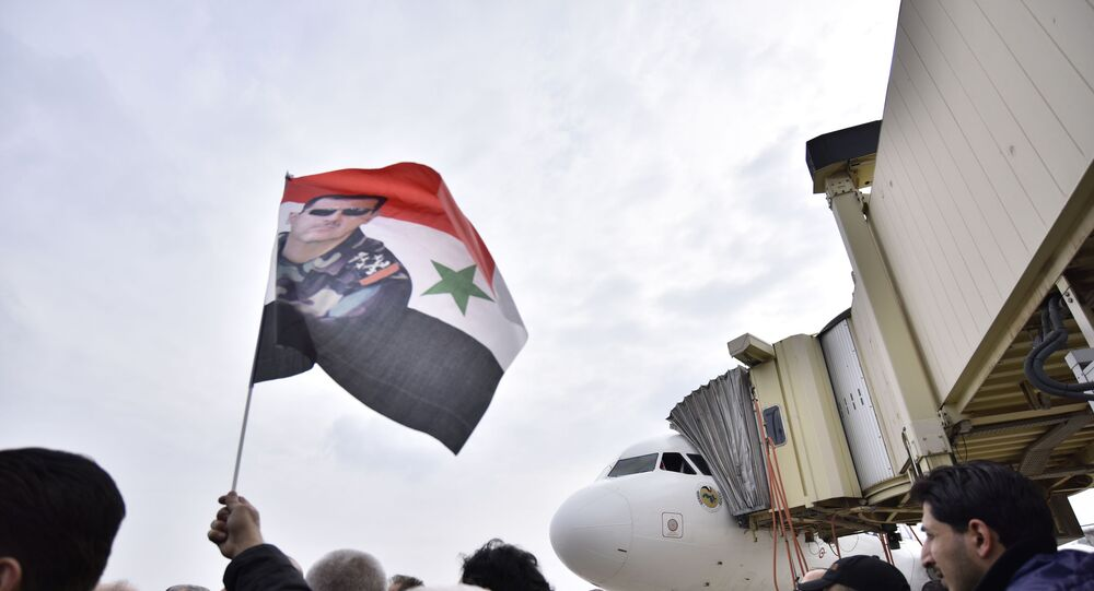 Homem levanta bandeira da Síria com imagem de Bashar Assad