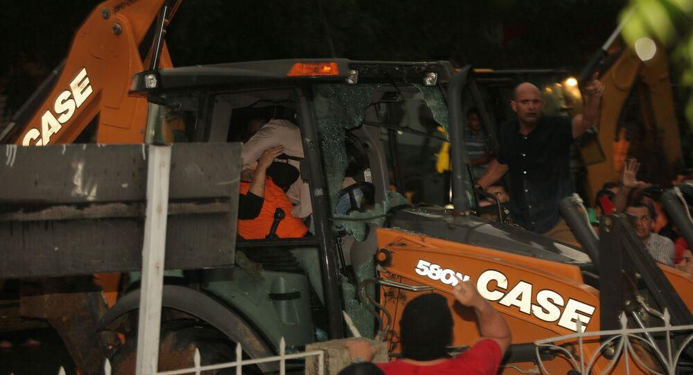 senador licenciado Cid Gomes (PDT) (de camiseta laranja) dirige retroescavadeira durante protesto de policiais na cidade de Sobral, no interior do Ceará, na tarde de quarta-feira (19)