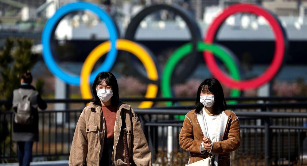 Pedestres utilizam máscara protetora próximo ao símbolo das Olimpíadas de Verão de Tóquio, programadas para serem iniciadas em julho de 2020