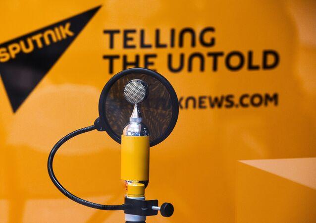 Microfone com logo da Sputnik ao fundo