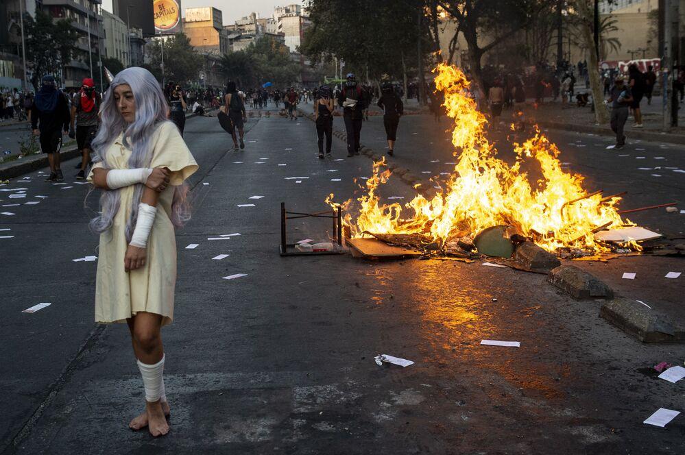 Manifestante em frente a fogueira ateada durante protestos contra o presidente do Chile, Sebastián Piñera, em 28 de fevereiro de 2020