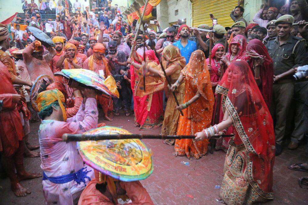 Mulheres batem em homens com uma vara durante as comemorações do festival hindu Lathmar, em 4 de março de 2020