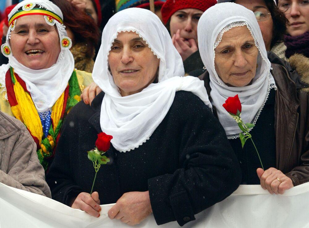 Mulheres curdas na Turquia com flores durante manifestação no Dia Internacional da Mulher em Istambul, 8 de março de 2005