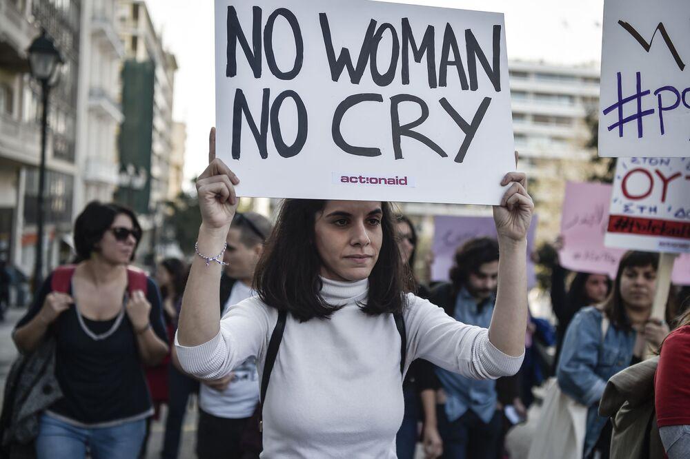 Mulher com cartaz com palavras da canção de Bob Marley, durante manifestação em Atenas, Grécia, 8 de março de 2019