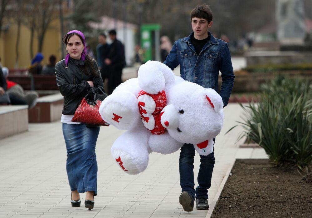 Jovem com urso de peluche de presente na véspera da festa de 8 de março na cidade de Grozny, república da Chechênia, Rússia