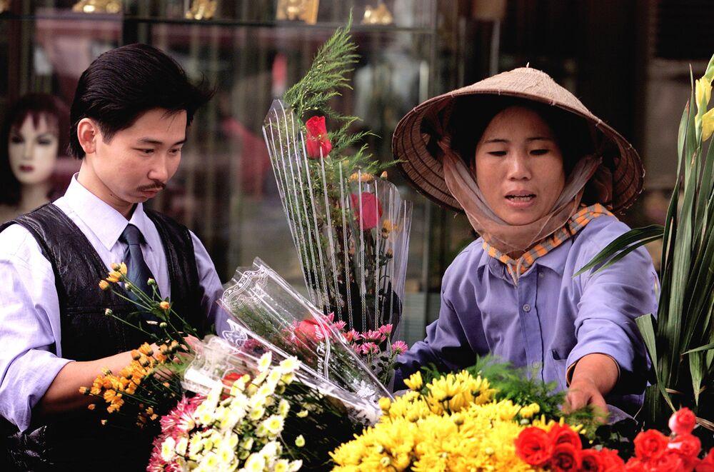 Jovem vietnamita compra rosa para menina em uma rua de Hanói, Vietnã, 8 de março de 2006
