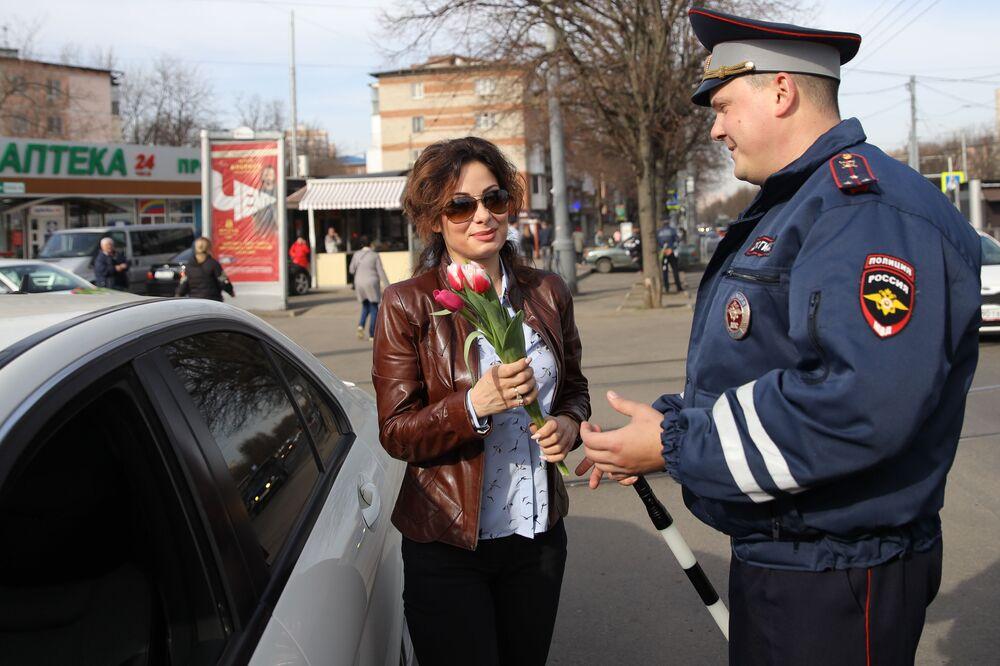 Inspetor da Patrulha Rodoviária da cidade russa de Krasnodar oferecendo flores no Dia Internacional da Mulher