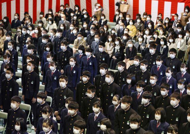 Estudantes usando máscaras protetoras após surto da doença coronavírus (COVID-19), participam da cerimônia de formatura em uma escola de ensino médio em Osaka, no oeste do Japão, 13 de março de 2020