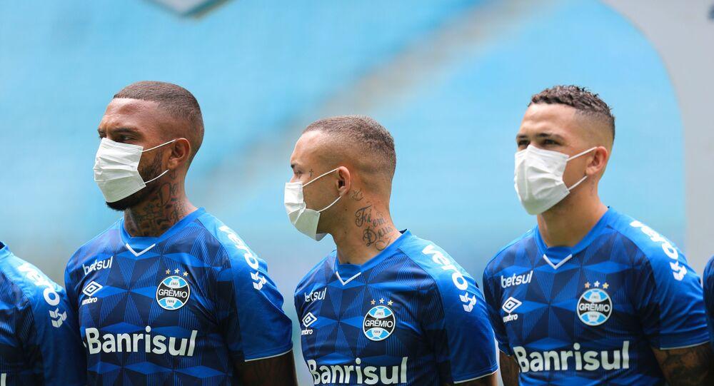 Jogadores do Grêmio usam máscaras antes da partida contra o São Luiz, com portões fechados, pelo Campeonato Gaúcho